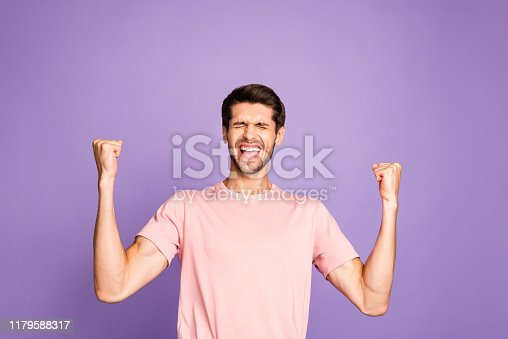 1092211952 istock photo Portrait of his he nice attractive virile muscular cheerful cheery satisfied guy wearing pink tshirt celebrating incredible attainment isolated on violet purple lilac pastel color background 1179588317
