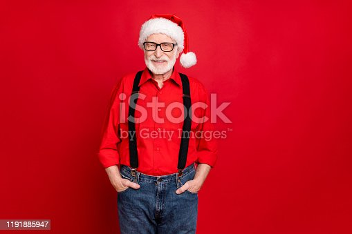 1165538246 istock photo Portrait of his he nice trendy cheerful kind content bearded Santa Claus wearing eyewear holding hands in pockets isolated over bright vivid shine vibrant red background 1191885947