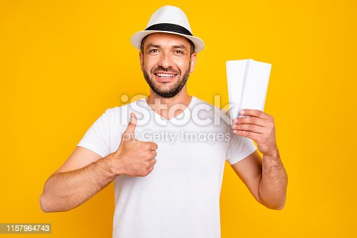 1165538246 istock photo Portrait of his he nice-looking attractive cheerful cheery glad guy wearing white t-shirt holding in hand tickets showing thumbup advert ad advice isolated over bright vivid shine yellow background 1157964743