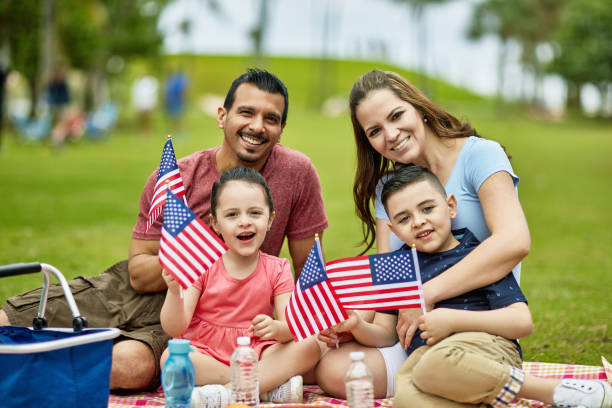 Portrait of Hispanic Family Celebrating American Holiday Smiling Hispanic American parents in late 30s with 4 and 6 year old children holding American flags and celebrating holiday with picnic at Miami park. family 4th of july stock pictures, royalty-free photos & images