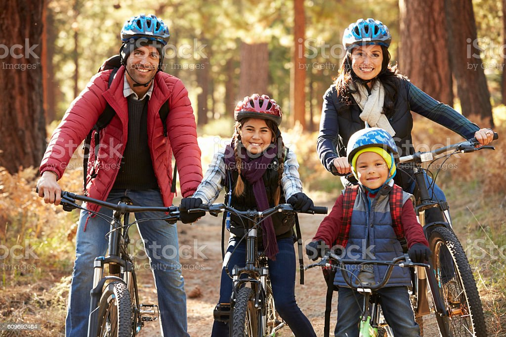Portrait of Hispanic family on bikes in a forest - foto de acervo