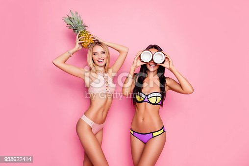 700603062istockphoto Portrait of hot, charming, stylish, pretty, trendy, crazy ladies, tourists in swim suits, blonde having ananas on her head, brunette having coconut on eyes' place, standing over pink background 938622414
