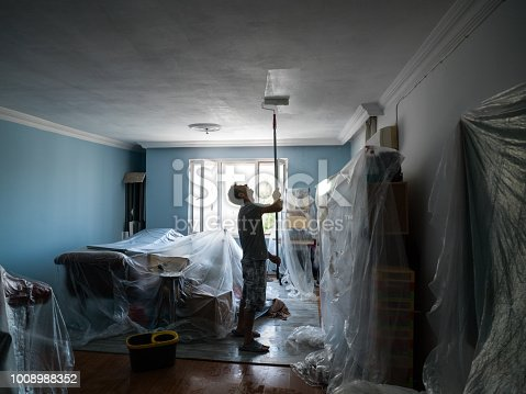 Portrait of adult house painter painting home interior. He is wearing a gray t-shirt and a plaid short. Shot indoor with a medium format camera.