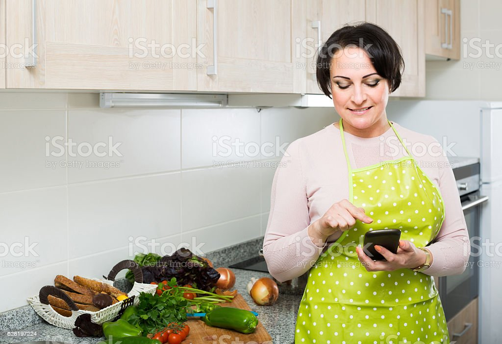 Portrait of  housewife in apron receiving sms with recipe stock photo