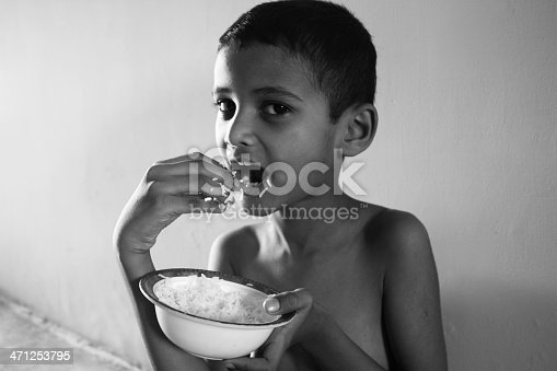 941788480 istock photo Portrait of hungry African kid eating rice 471253795