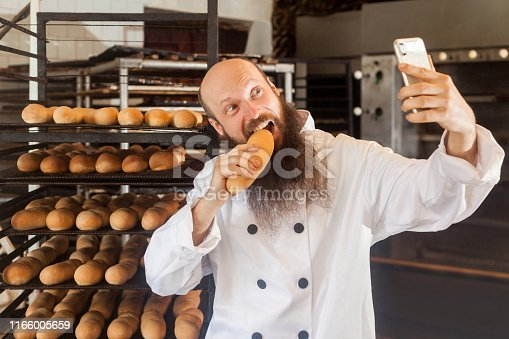 istock Portrait of hungry young adult blogger baker with long beard in white uniform standing in factory and making selfie on shelves with fresh bread background 1166005659