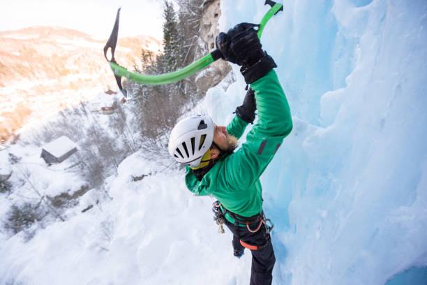 portrait of ice climber hitting the ice with his axe - アイスクライミング ストックフォトと画像