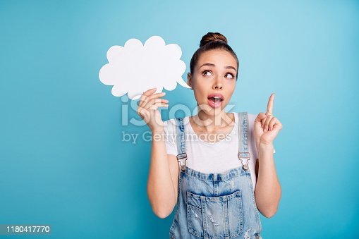 Portrait of impressed lovely girl showing her index finger holding paper, card bubble wearing white t-shirt denim jeans overalls isolated over blue background