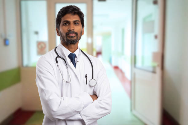 Portrait of indian doctor Portrait of male indian doctor with serious expression and crossed arms wearing white coat having open door on clinic corridor as background indian male stock pictures, royalty-free photos & images
