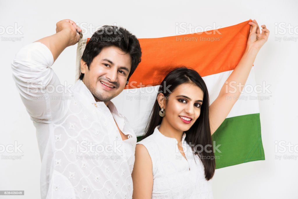 Portrait of indian happy young couple in ethnic wear holding Indian flag. Asian handsome young man and woman and indian tricolour or flag. Standing isolated over white background stock photo