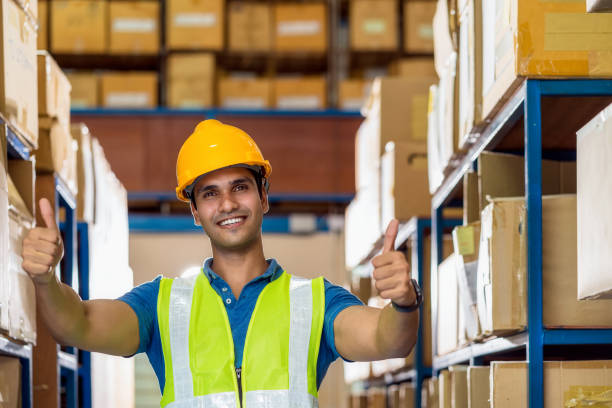 Portrait of Indian warehouse worker man with safety clothes standing with confident and showing thumps up