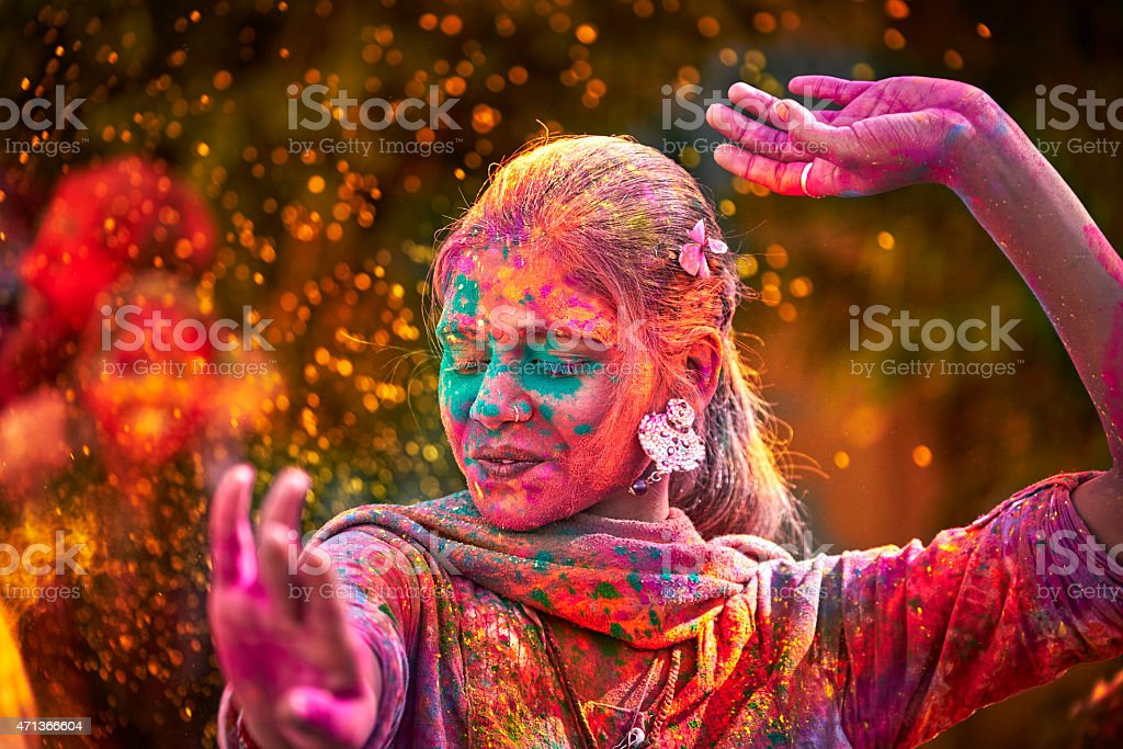 Portrait Of Indian Woman With Colored Face Dancing During Holi stock photo