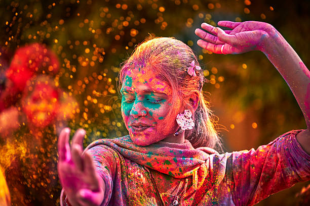 portrait of indian woman with colored face dancing during holi - cultures stock pictures, royalty-free photos & images