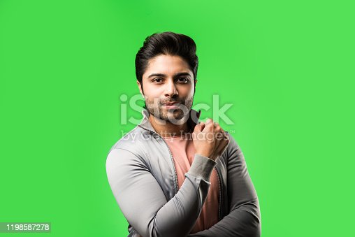 Portrait of Indian Young Man, standing isolated over green chroma key background