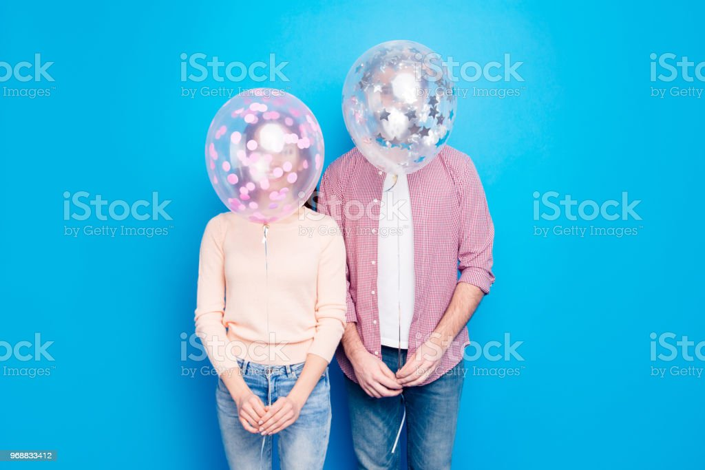Portrait of interesting crazy couple closing head with air balloons...