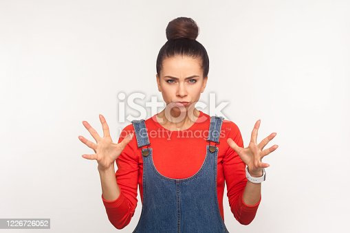 808681534 istock photo Portrait of irritated annoyed stressed girl with hair bun in denim overalls standing with clenched teeth and raised hands 1226726052