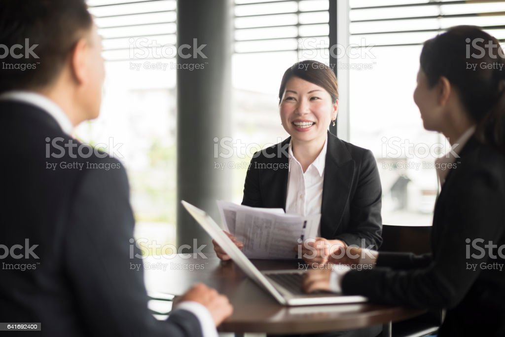 Portrait of Japanese businesswoman in meeting, colleague using laptop stock photo