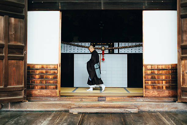 Portrait of Japanese Monk at Temple A Japanese monk is on errand and walking at the Chion-ji Temple in Kyoto Japan. He is holding a message while walking in the main entrance to the temple. He is of the Jodu-shu religion.  shinto stock pictures, royalty-free photos & images