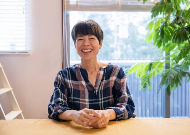 食堂に座っている日本人の母親の肖像 - 女性 笑顔 ストックフォトと画像