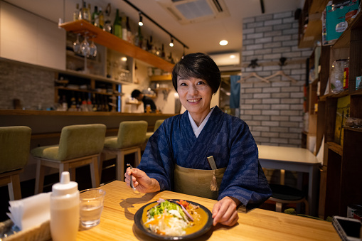 Portrait of Japanese woman in kimono eating curry for lunch in cafe