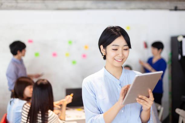 デジタル タブレットを保持している間日本の若いビジネス ・ ウーマンの肖像画 ストックフォト