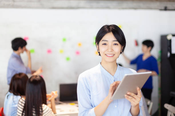 デジタル タブレットを保持している間日本の若いビジネス ・ ウーマンの肖像画 - 歯を見せて笑う ストックフォトと画像