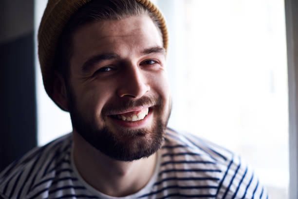 Portrait of jolly handsome young bearded sailor with kind face wearing hat and sweater smiling at camera cheerfully Portrait of jolly sailor sailor suit stock pictures, royalty-free photos & images