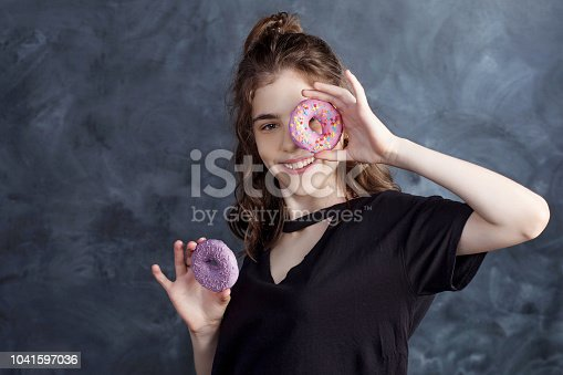 692840848istockphoto Portrait of joyful girl covering her eyes with donuts on black background. Attractive girl holding fresh donuts and having fun with sweet-stuff. Good mood, diet concept. 1041597036