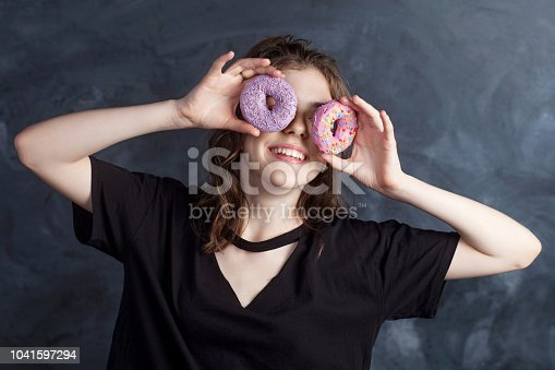 692840848istockphoto Portrait of joyful girl covering her eyes with donuts on black background. Attractive girl holding fresh donuts and having fun with sweet-stuff. Good mood, diet concept. 1041597294