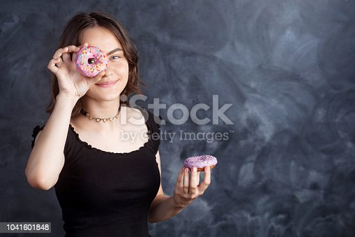 692840848istockphoto Portrait of joyful girl covering her eyes with donuts on black background. Attractive girl holding fresh donuts and having fun with sweet-stuff. Good mood, diet concept. 1041601848