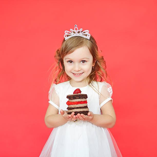 portrait of joyful little girl with cake celebrating her birthday - prinzessinnen torte stock-fotos und bilder