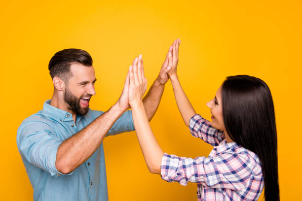 Portrait of joyful lucky couple giving high five with two hands enjoying victory in competition isolated on vivid yellow background Portrait of joyful lucky couple giving high five with two hands enjoying victory in competition isolated on vivid yellow background encouragement stock pictures, royalty-free photos & images