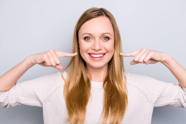 一個快樂滿意的女孩的肖像示意她喜氣洋洋的白色健康的牙齒與兩個食指看著相機孤立的灰色背景。正畸概念 - 微笑 個照片及圖片檔