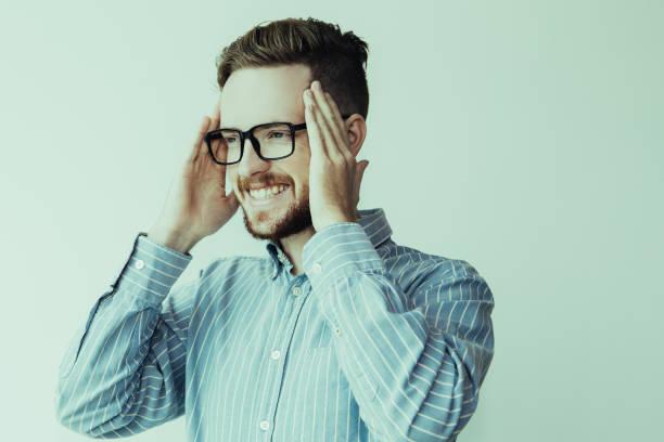 porträt von fröhlichen jungen mann in gläser kopf berühren - scheuklappe stock-fotos und bilder