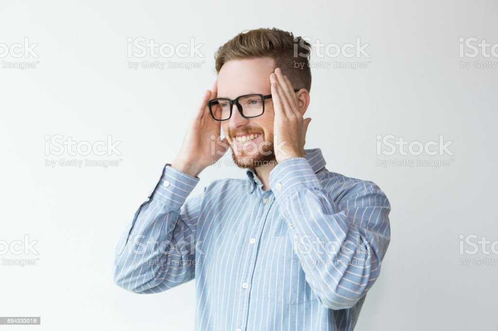 Portrait of Joyful Young Man In Glasses Touching Head stock photo