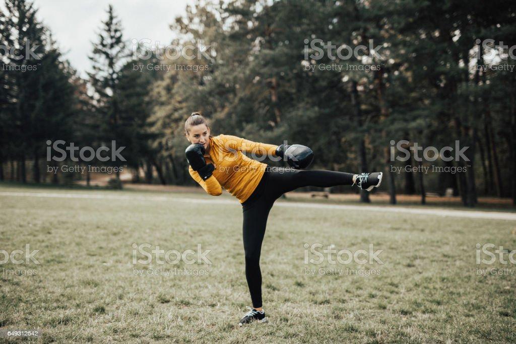 Portrait of kickboxing woman doing a kick stock photo
