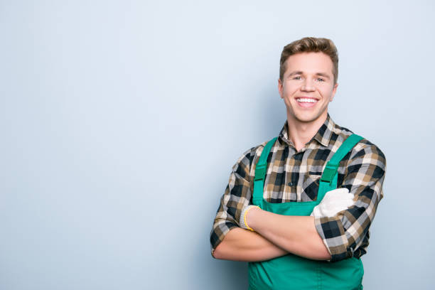 Portrait of kind cheerful excited smart professional friendly expert handsome with beaming shiny smile handyman wearing green overalls standing with folded hands isolated on gray background copyspace Portrait of kind cheerful excited smart professional friendly expert handsome with beaming shiny smile handyman wearing green overalls standing with folded hands isolated on gray background copyspace bib overalls stock pictures, royalty-free photos & images