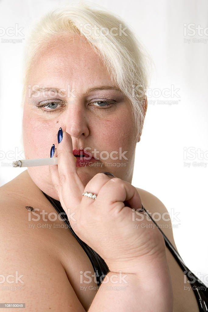 Portrait of large scantily dressed woman smoking. stock photo