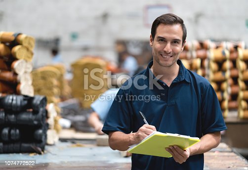 Portrait of latin american supervisor at a shoe factory holding a clipboard and pen while facing camera smiling very happy