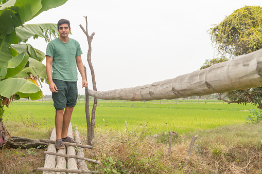 Portrait of latin young fit male farmer walking to a bamboo bridge, on back, an organic rice paddy wheat field terrace at a farmland. \n\nSmiling young male farm owner working and preparing harvest organic wheat crop plant in Ecuador. Agriculture product industry concept.