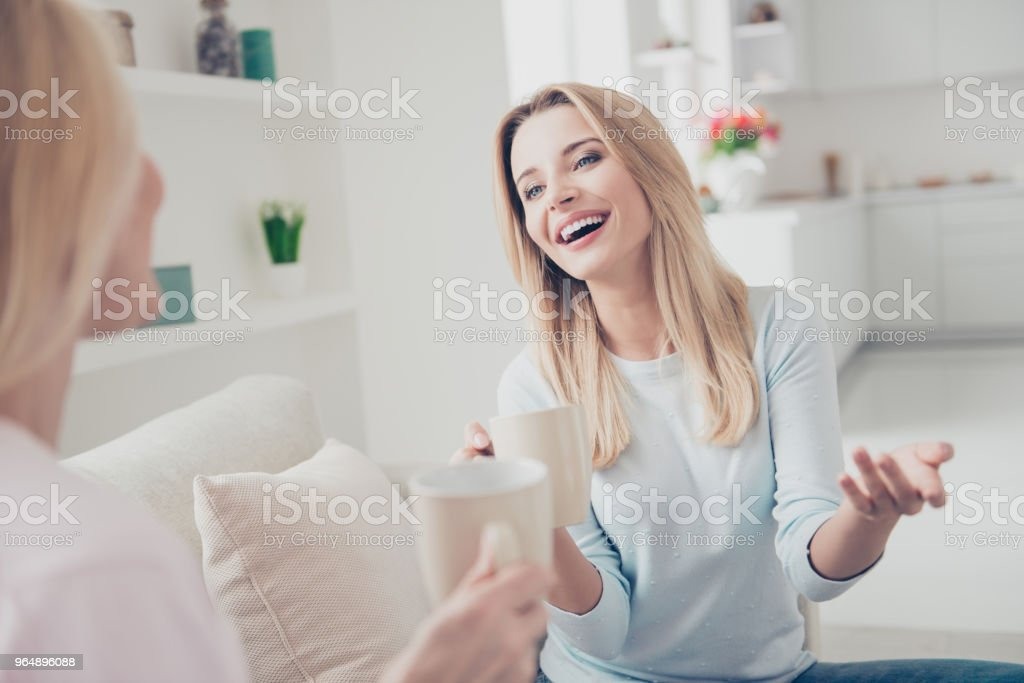 Portrait of laughing cheerful positive girl joking sharing secrets with her mother having mugs with tea cacao beverage in hands cozy comfort atmosphere enjoying meeting indoor sitting on sofa royalty-free stock photo