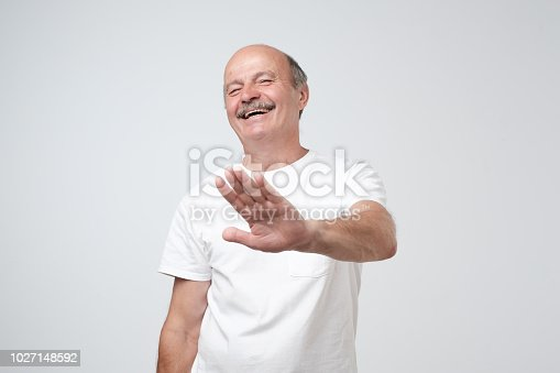 istock Portrait of laughing mature man wearing white t-shirt showing stop gesture with palm, laughing on funny joke. 1027148592