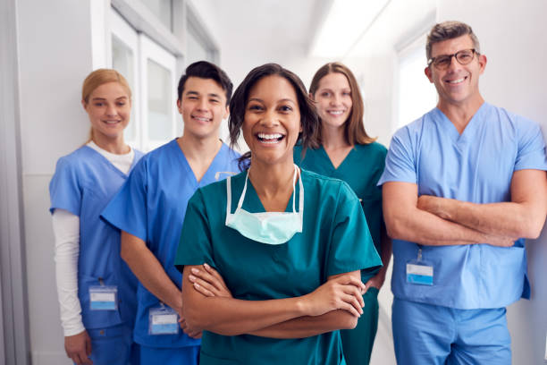 Portrait Of Laughing Multi-Cultural Medical Team Standing In Hospital Corridor Portrait Of Laughing Multi-Cultural Medical Team Standing In Hospital Corridor nurses stock pictures, royalty-free photos & images