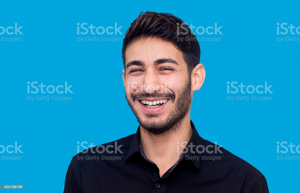 Portrait of laughing young man against blue background stock photo