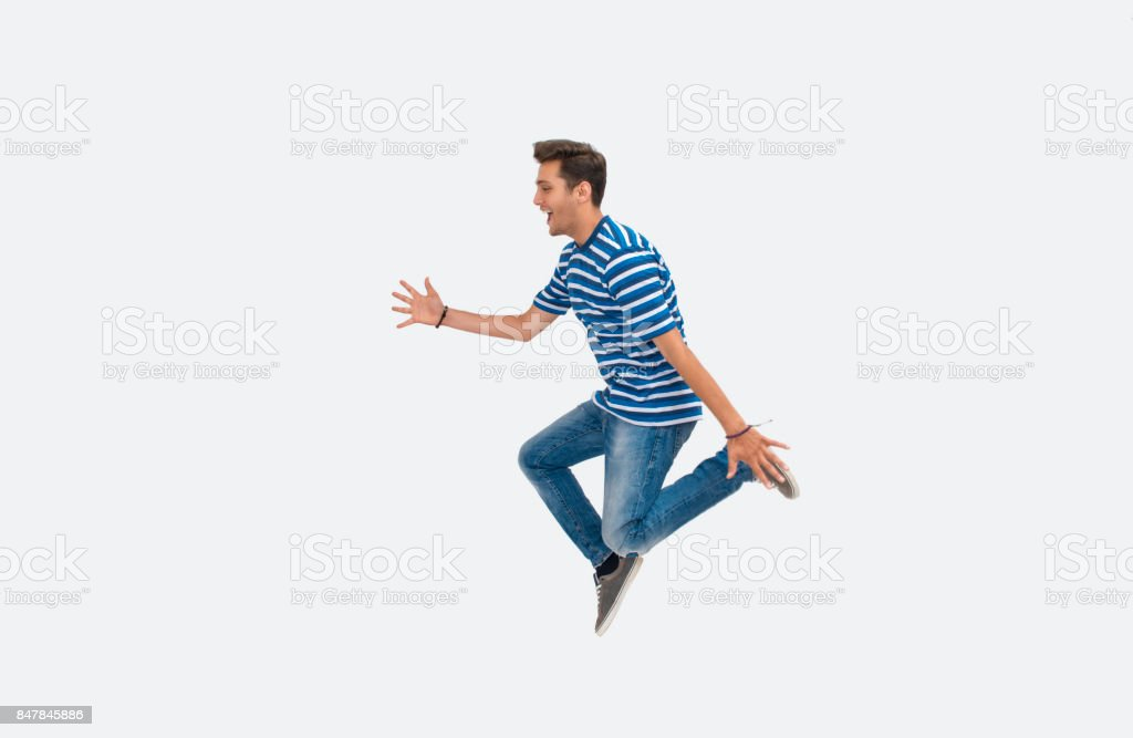 Portrait of laughing young man jumping on white background stock photo