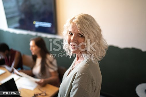 949435100 istock photo Portrait of leader mature businesswoman at conference table 1209985797