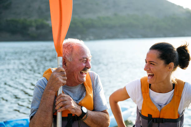 portrait of lighthearted senior kayaker and paddling friend - sud europeo foto e immagini stock