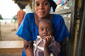 Katunguru, Uganda - October 20, 2016: Portrait of little African girl with her mother on the street