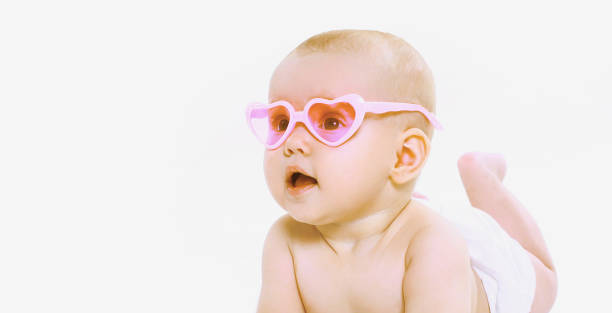 Portrait of little baby wearing a summer pink heart shaped sunglasses and diapers looking away over a white background stock photo