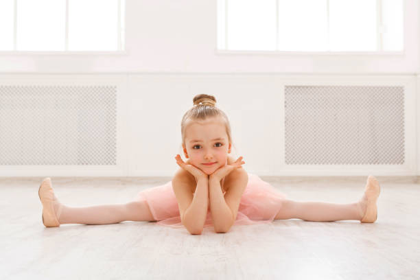 Portrait of little ballerina on floor, copy space stock photo